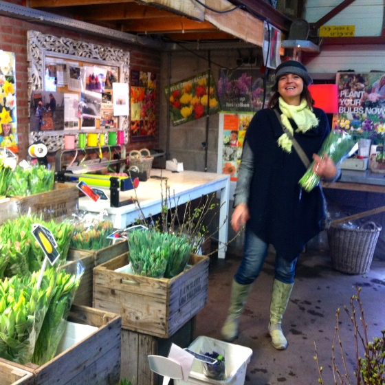 vrouw met bos bloemen in bloemenwinkeltje