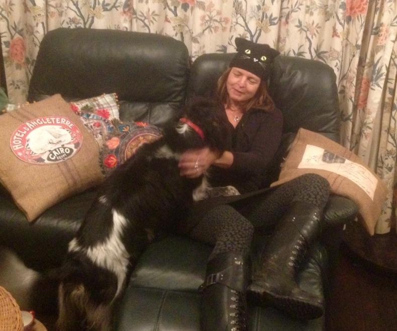 vrouw met hond, op bank, liefde tssen mens en dier,vrouw verkleed als kat, kattenmuts,  liefde tussen vrouw en hond, vrouw knuffelt hondje