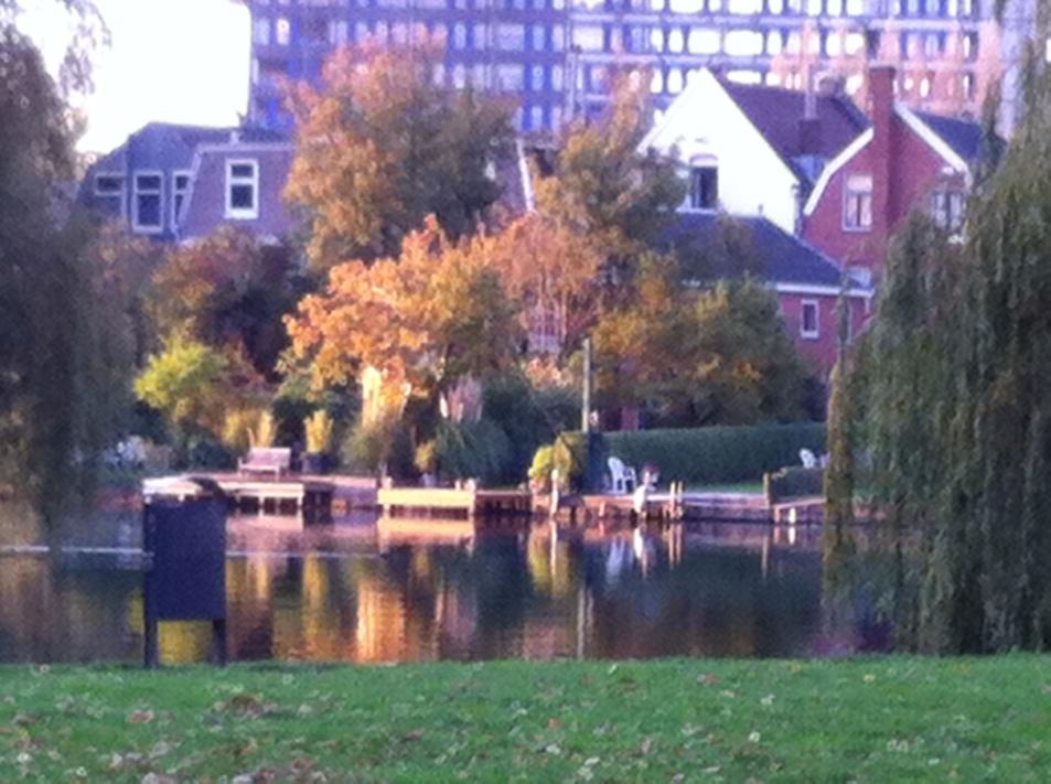 Leiden, herfst, mooie lucht, gloeiende kleuren ligstoelen in park, huizen langs de Rijn