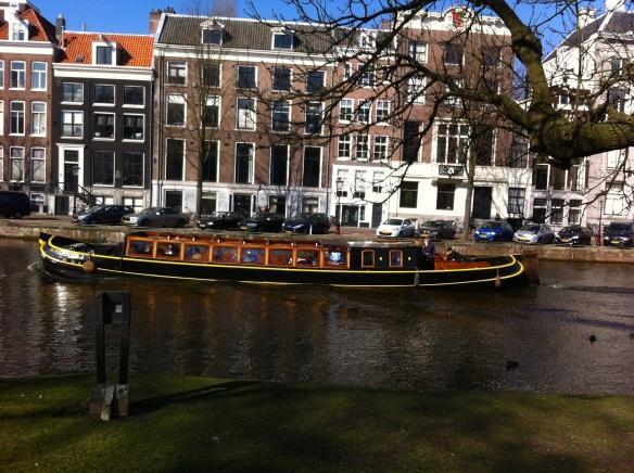 lente, surfers op Amsterdamse grachten, rondvaartboot