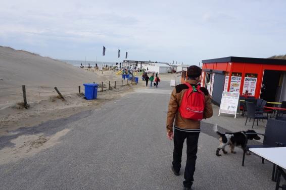 knappe man aan het strand, oprit naar strand, kust, Wassenaarse Slag, hond en man,. balletje gooien, Scheveningen in de verte